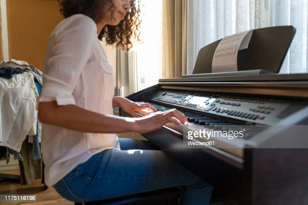 woman playing piano at home - keyboard player stock photos and pictures