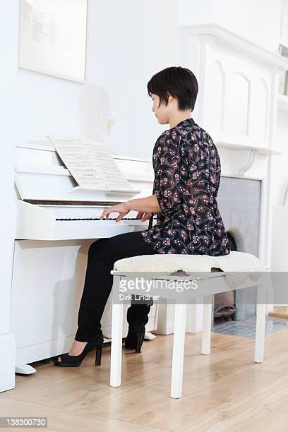 woman playing piano at home - ピアノ奏者 ストックフォトと画像