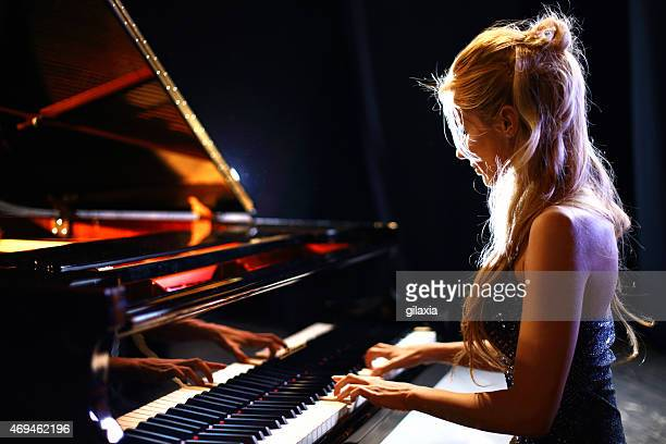 woman playing piano in a concert. - grand piano stock photos and pictures