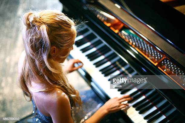 woman playing piano in a concert. - plucking an instrument stock pictures, royalty-free photos & images