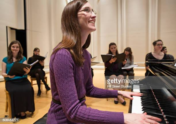 woman playing piano with choir on stage - keyboard player stock photos and pictures
