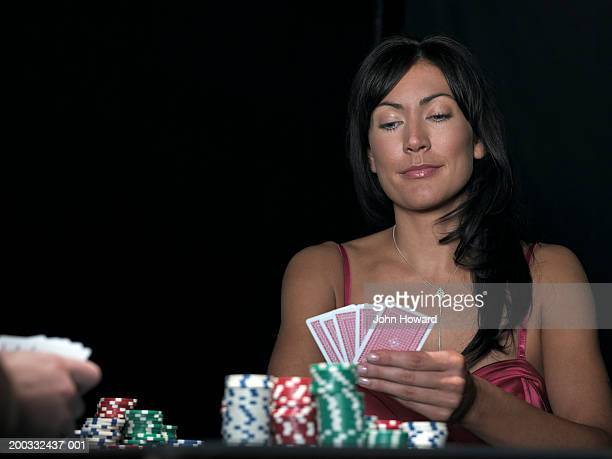 Woman playing poker, looking at hand