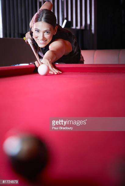 Woman playing pool and smiling