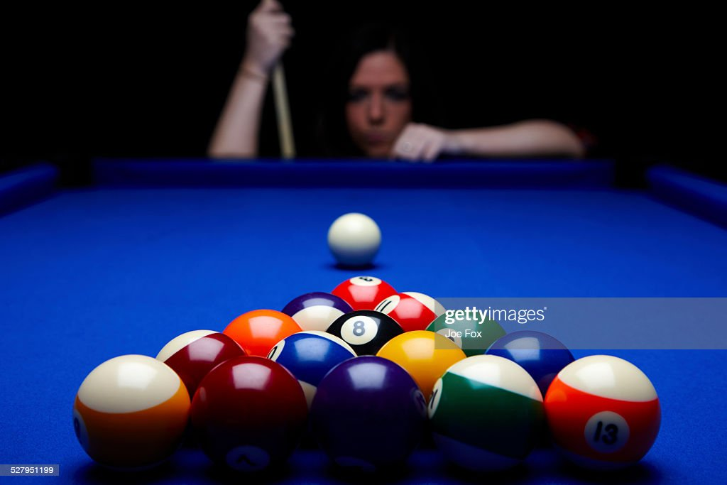Woman playing pool with balls set on table : Stock Photo