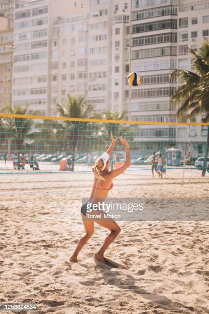 woman playing professional beach volleyball at copacabana beach in rio de janeiro - beach volleyball stock pictures, royalty-free photos & images