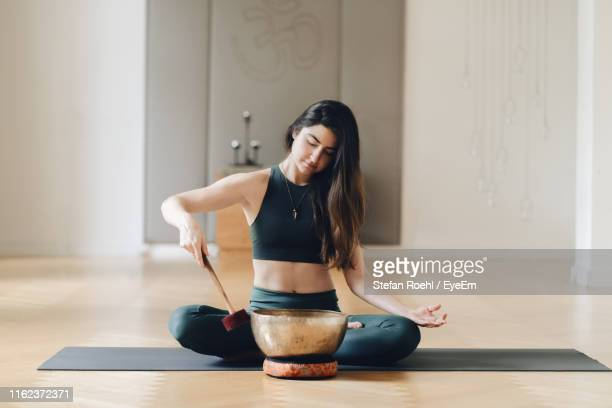 woman playing rin gong while sitting on exercise mat - gong stock pictures, royalty-free photos & images