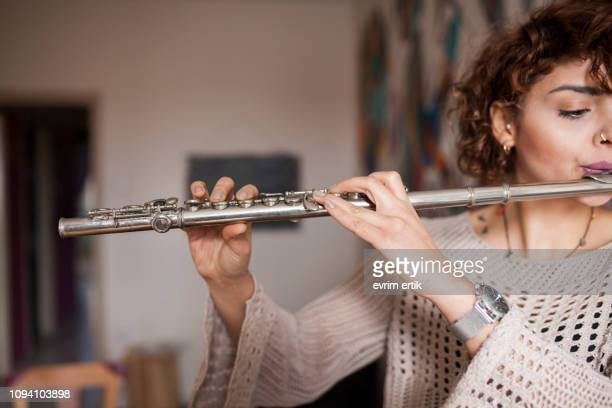 woman playing silver hole c flute - classical musician stock pictures, royalty-free photos & images