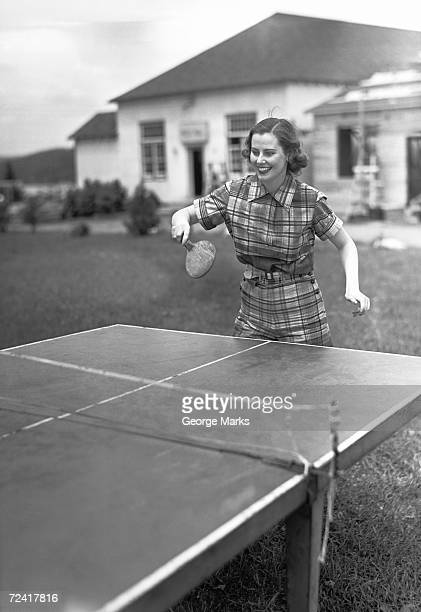 Woman playing table tennis in garden, (B&W)