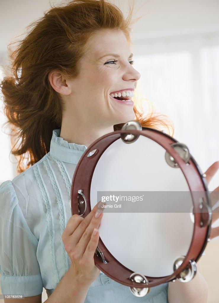 Woman playing tambourine : Stock Photo