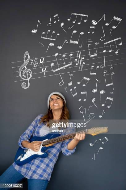 woman playing the guitar and looking at musical notes on a blackboard - chalk wall stock pictures, royalty-free photos & images