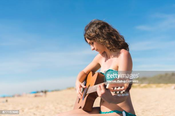 Woman playing the guitar in the beach