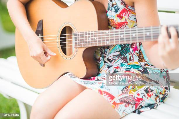woman playing the guitar in the garden - songwriter stock pictures, royalty-free photos & images