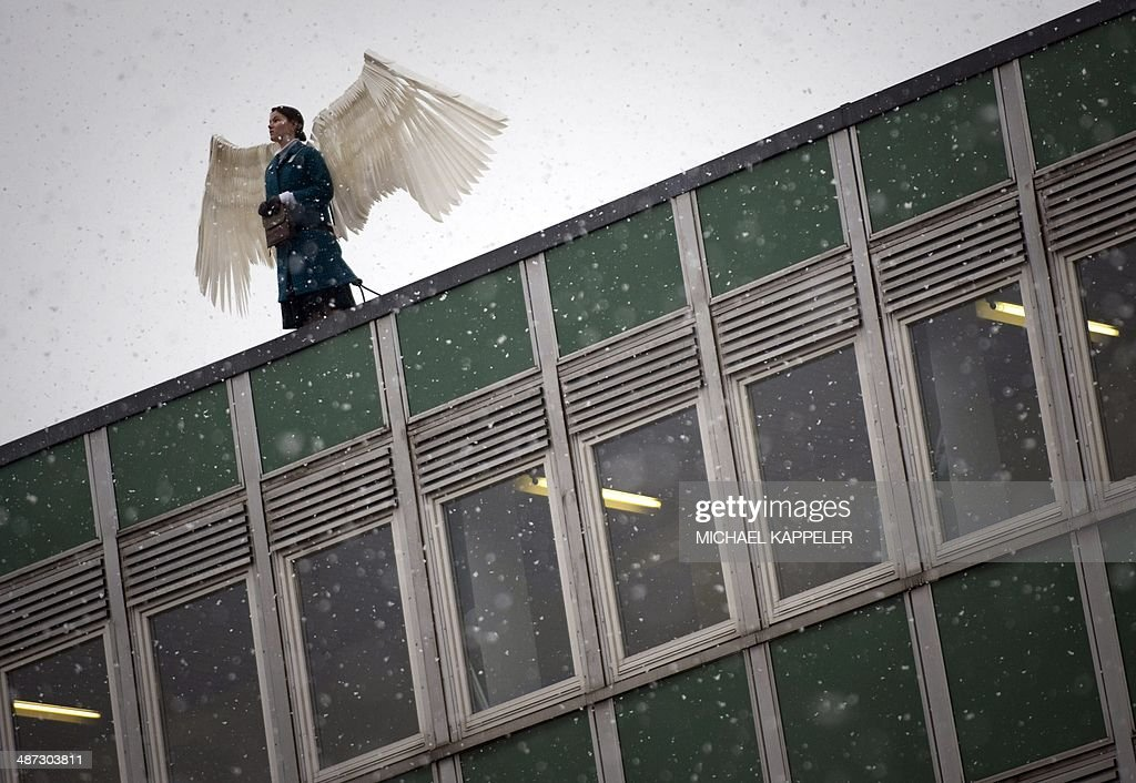A woman playing the part of an angel takes part in a dress rehearsal for a theatre piece of a rooftop in Berlin on November 4, 2009. The theatre piece will take place on November 9, 2009 during the 20th anniversary celebrations of the fall of the Wall.