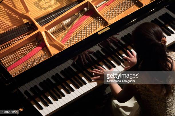 woman playing the piano - grand piano stock photos and pictures