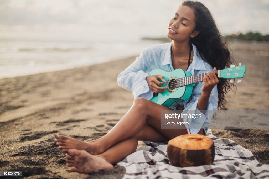 Woman playing ukulele at the beach : Stock Photo