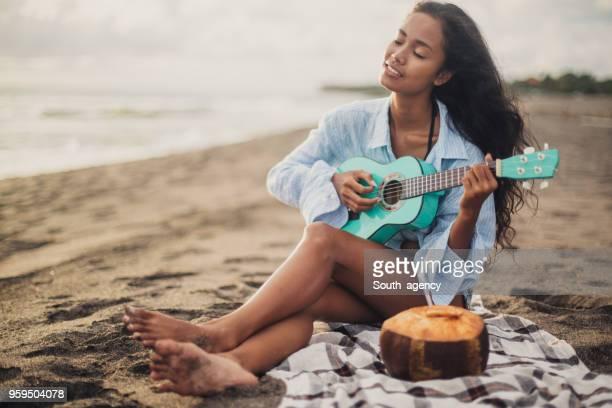 frau spielt ukulele am strand - ukulele stock-fotos und bilder