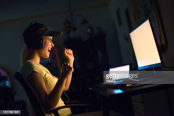 woman playing video game on desktop pc at home - alleen volwassenen stockfoto's en -beelden