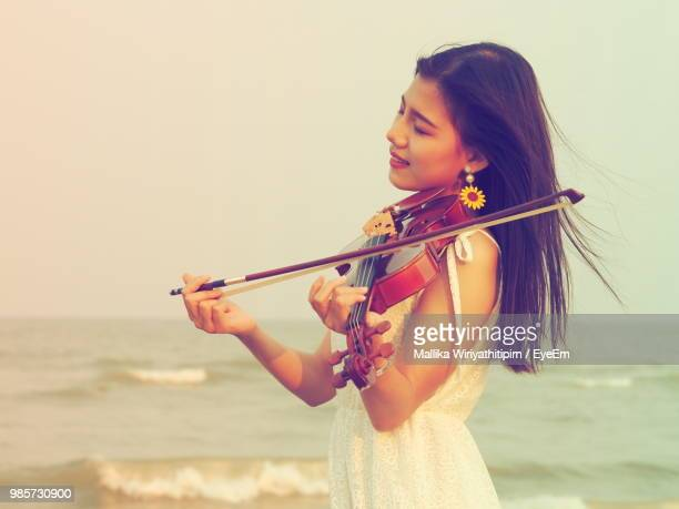 Woman Playing Violin By Sea Against Clear Sky