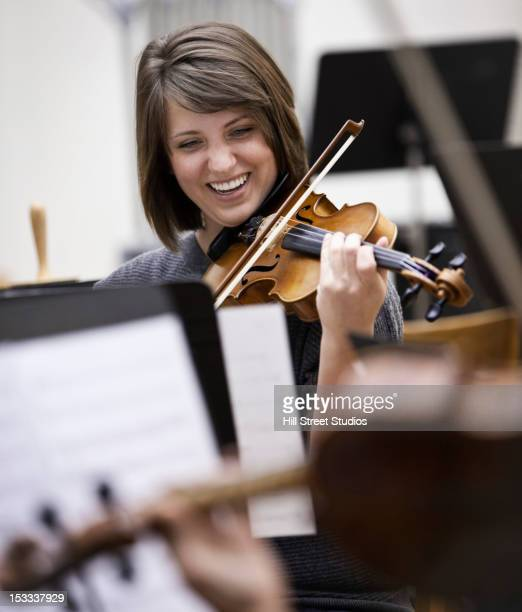 woman playing violin in orchestra - practicing stock pictures, royalty-free photos & images