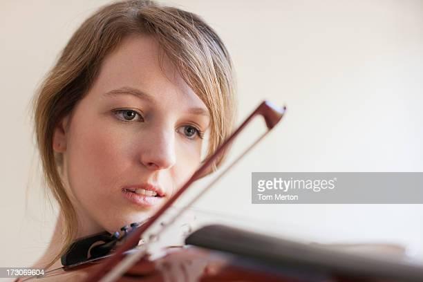 Frau spielt Violine in der Nähe vom Fenster nachdenkt.