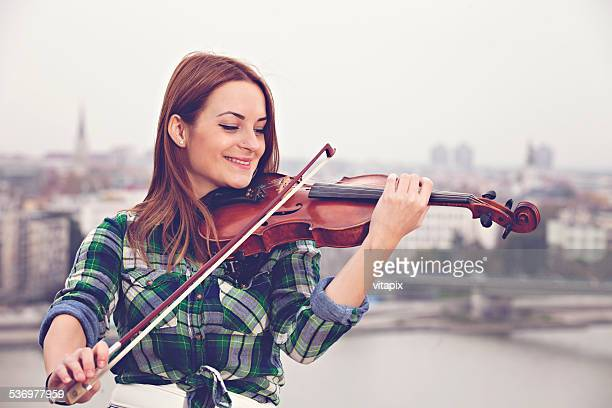 Woman playing violin outdoors