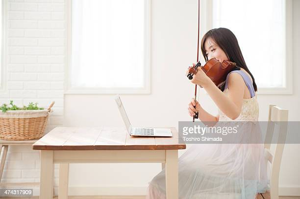 A woman playing violin with an eye on the laptop