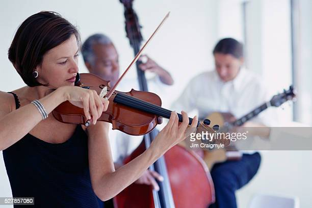Woman Playing Violin with Other Musicians