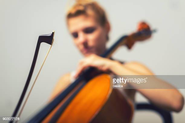 woman playing violoncello on the stage - cellist stock pictures, royalty-free photos & images