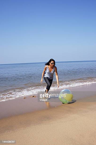 Woman playing with a ball at the beach