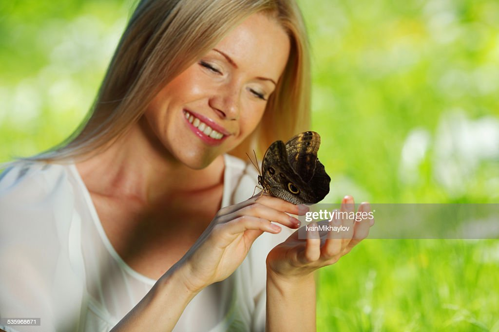 Woman playing with a butterfly : Stock Photo