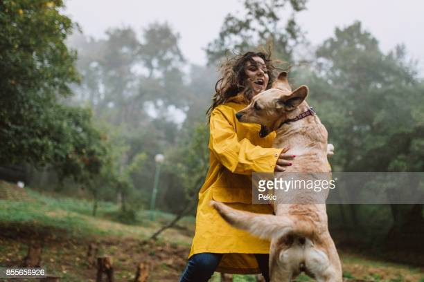 Woman playing with a dog in the woods