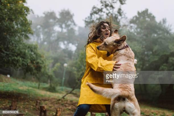 Vrouw speelt met een hond in het bos