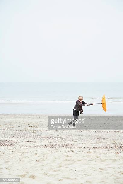 Woman playing with an umbrella in the wind