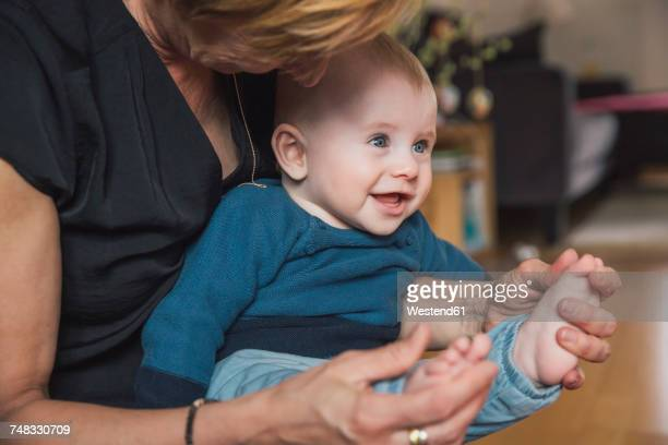 Woman playing with baby boy's feet at home