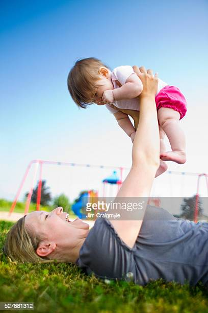 woman playing with baby daughter (6-12 months) on lawn - 12 23 months stock pictures, royalty-free photos & images