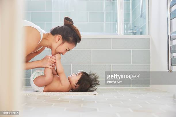 woman playing with baby daughters feet on bathroom floor - diaper girl photos et images de collection