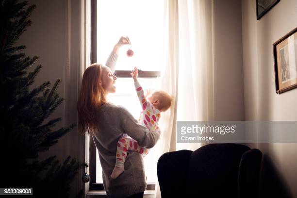 Woman playing with baby girl while standing by window at home