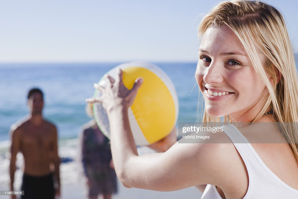 Woman playing with ball on beach : Stock Photo