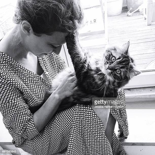Woman Playing With Cat While Sitting On Window Sill At Home