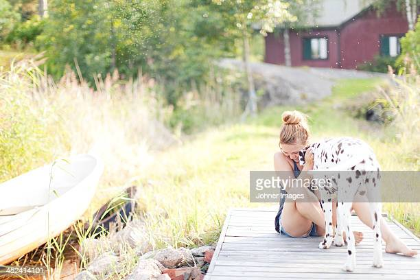 Woman playing with Dalmatian dog at jetty