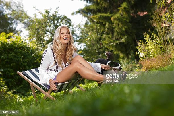 Frau spielen mit dem Hund im Garten