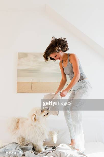 Woman playing with dog in bed