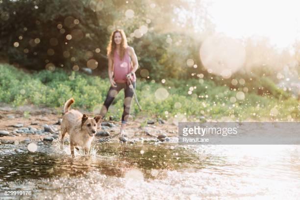 川で犬と遊ぶ女性