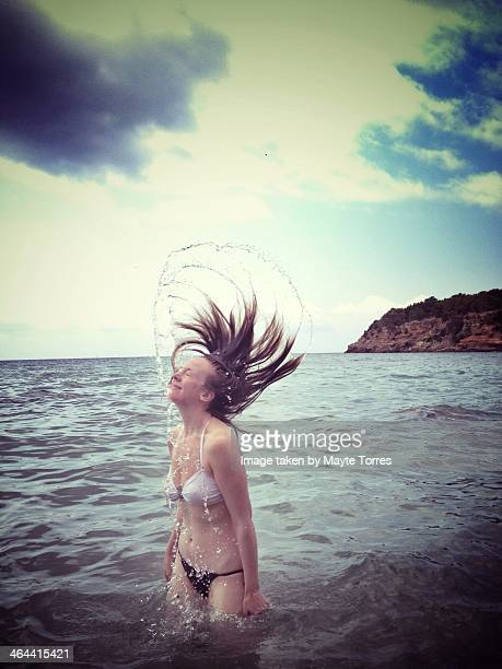 Woman playing with hair and water at the beach