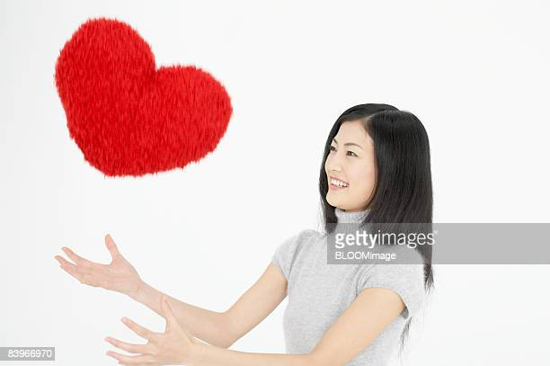 Woman playing with heart shaped cushion