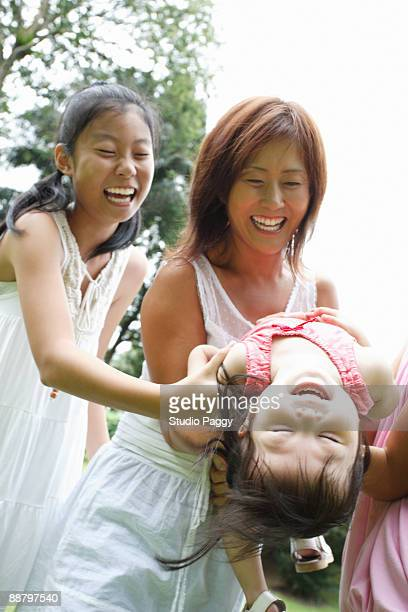 Woman playing with her daughters in a park