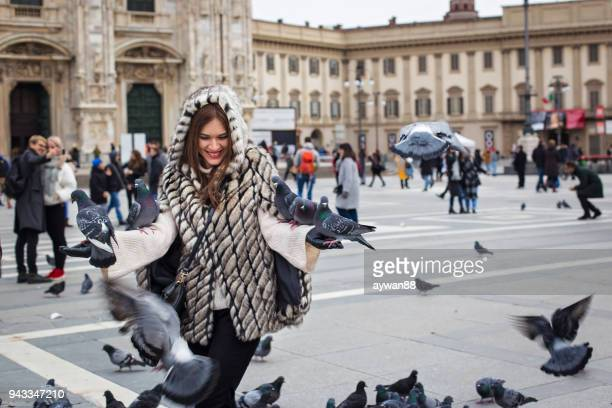 woman playing with pigeons - milan stock pictures, royalty-free photos & images