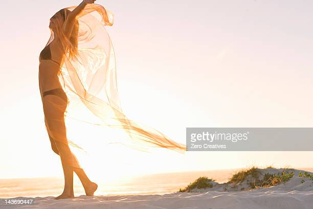 woman playing with sarong on beach - sarong stock photos and pictures