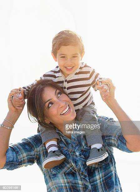 woman playing with son (2-3) - carrying a person on shoulders stock photos and pictures
