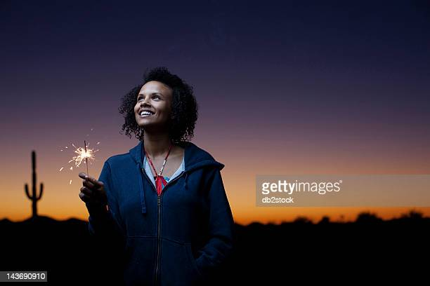 Woman playing with sparkler in desert
